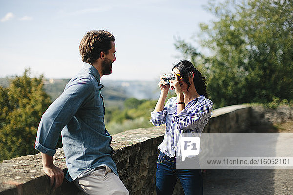Woman photographing boyfriend standing by retaining wall with camera against sky
