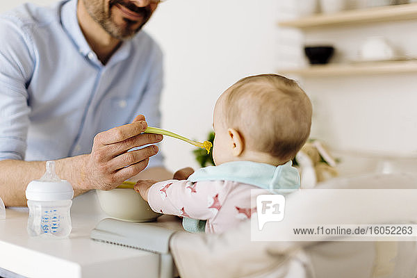 Vater füttert kleines Mädchen im Hochstuhl Vater füttert kleines Mädchen im Hochstuhl