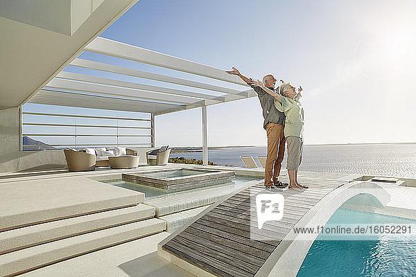 Unbeschwertes älteres Paar  das auf einer Brücke über einem Swimmingpool in einem luxuriösen Strandhaus steht Unbeschwertes älteres Paar, das auf einer Brücke über einem Swimmingpool in einem luxuriösen Strandhaus steht