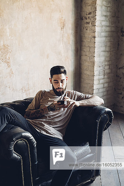 Young man sitting in armchair in a loft using smartphone