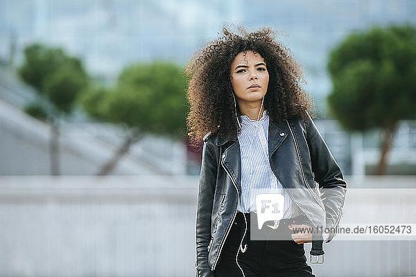 Selbstbewusste junge Afro-Frau  die im Stehen mit der Hand in der Tasche Musik hört Selbstbewusste junge Afro-Frau, die im Stehen mit der Hand in der Tasche Musik hört
