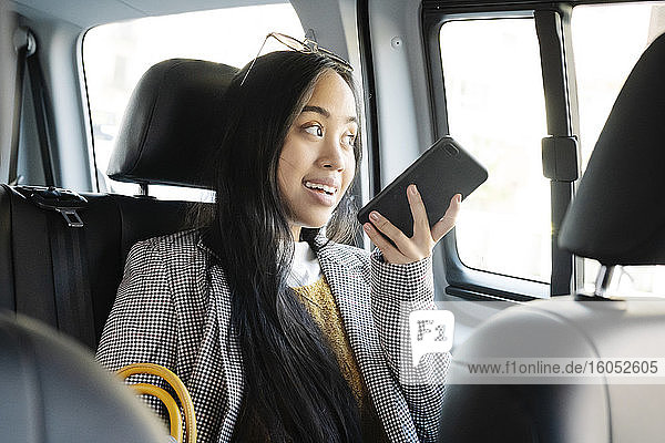 Woman talking over smart phone while sitting in taxi