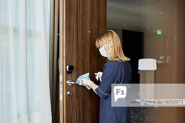 Zimmermädchen mit Maske beim Reinigen eines Türknaufs in einem Hotel Zimmermädchen mit Maske beim Reinigen eines Türknaufs in einem Hotel