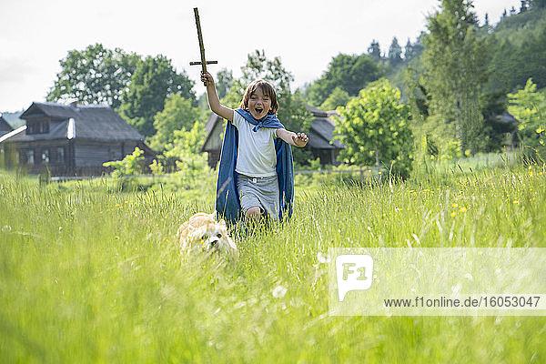 Verspielter Junge mit Umhang läuft mit Hund auf einer Wiese Verspielter Junge mit Umhang läuft mit Hund auf einer Wiese