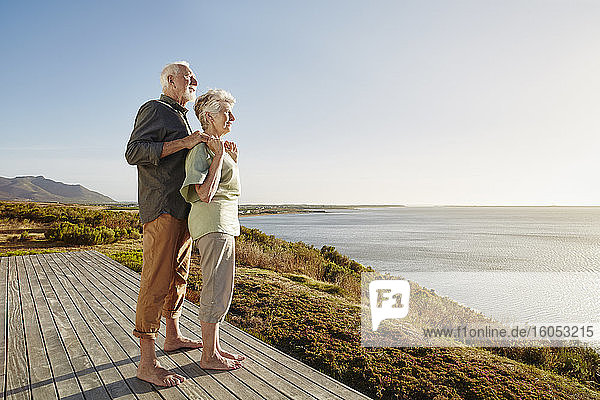 Senior couple enjoxing the view on wooden terrace at the sea
