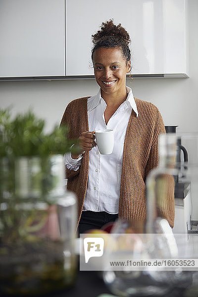 Portrait of smiling businesswoman standing in kitchen with cup of coffee