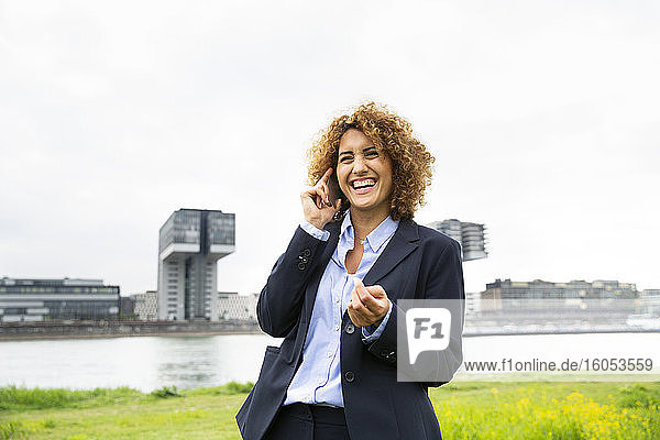 Cheerful female entrepreneur with curly hair talking over mobile phone while standing against sky in city