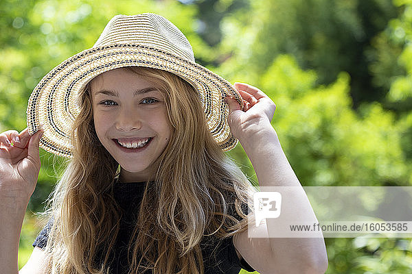 Close-up of carefree girl wearing hat against trees in park