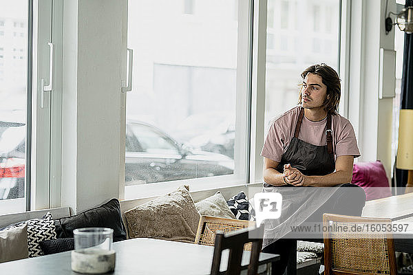 Thoughtful barista with hands clasped sitting on table in cafe