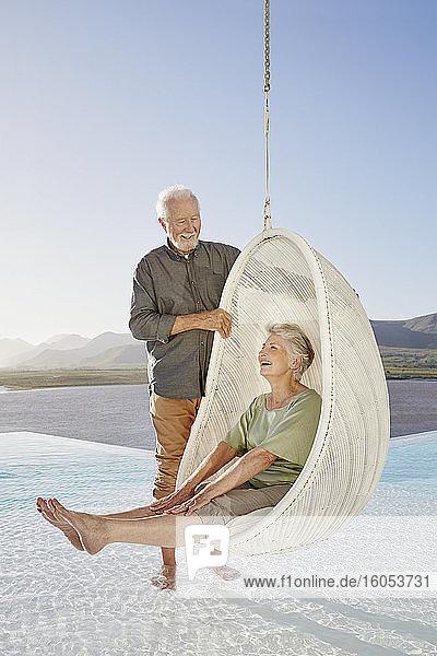 Glückliches älteres Paar mit Frau  die in einem Hängesessel über dem Schwimmbad sitzt Glückliches älteres Paar mit Frau, die in einem Hängesessel über dem Schwimmbad sitzt