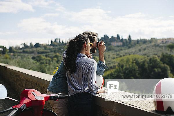 Frau steht neben ihrem Freund und fotografiert mit der Kamera Frau steht neben ihrem Freund und fotografiert mit der Kamera
