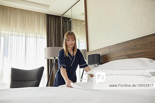 Zimmermädchen ordnet Laken auf dem Bett im Hotelzimmer Zimmermädchen ordnet Laken auf dem Bett im Hotelzimmer