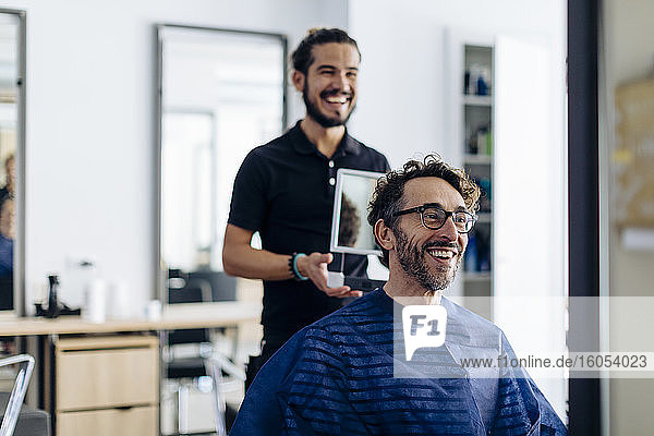 Glückliche Friseurin zeigt dem Kunden im Spiegel den Haarschnitt im Salon Glückliche Friseurin zeigt dem Kunden im Spiegel den Haarschnitt im Salon