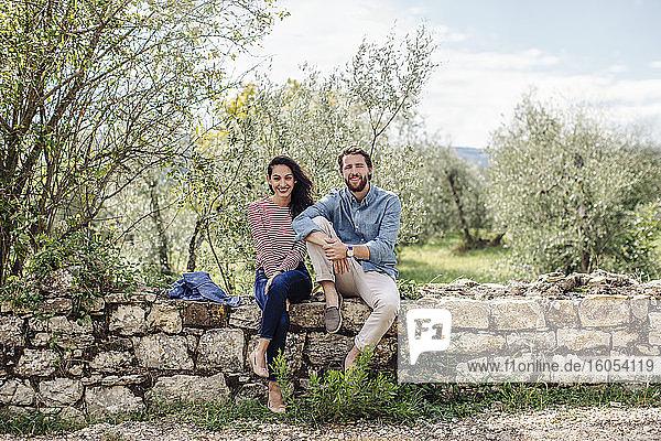 Lächelndes junges Paar sitzt auf einer Stützmauer vor Bäumen Lächelndes junges Paar sitzt auf einer Stützmauer vor Bäumen