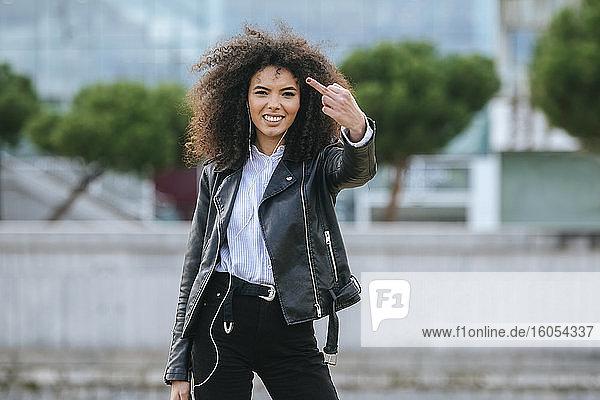 Glückliche junge Frau zeigt den Mittelfinger  während sie im Freien steht Glückliche junge Frau zeigt den Mittelfinger, während sie im Freien steht