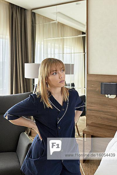 Nachdenkliches Zimmermädchen mit Händen in der Hüfte im Hotelzimmer stehend Nachdenkliches Zimmermädchen mit Händen in der Hüfte im Hotelzimmer stehend