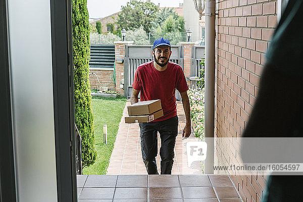 Lächelnder männlicher Postangestellter  der Pakete an eine ältere Frau ausliefert