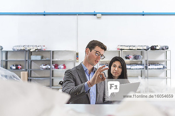 Businessman with laptop talking to female employee in a warehouse