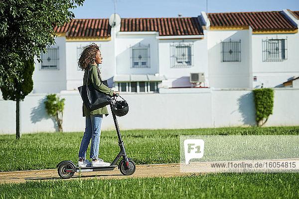 Junge Frau fährt in der Stadt mit einem Elektroroller Junge Frau fährt in der Stadt mit einem Elektroroller