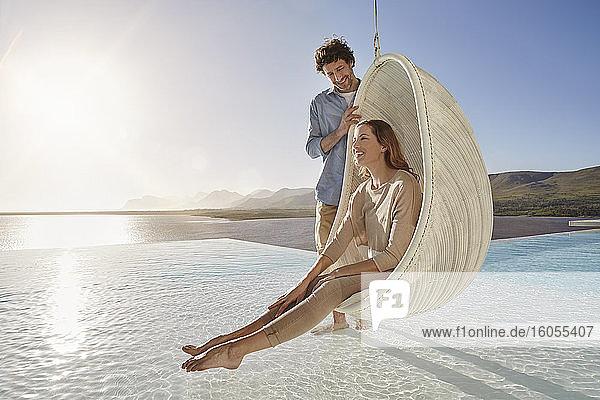 Glückliches Paar mit Frau in Hängesessel über Schwimmbad sitzend Glückliches Paar mit Frau in Hängesessel über Schwimmbad sitzend