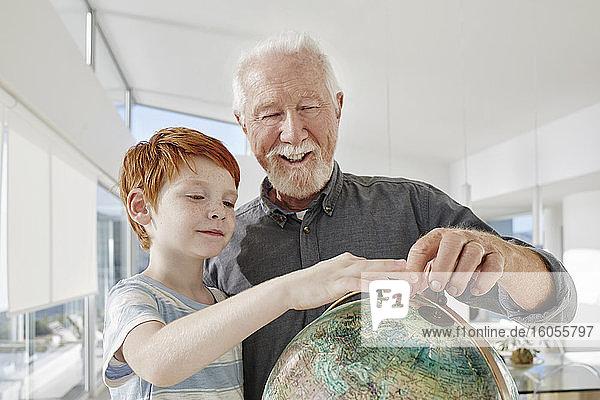 Großvater und Enkel betrachten den Globus in einer Villa Großvater und Enkel betrachten den Globus in einer Villa