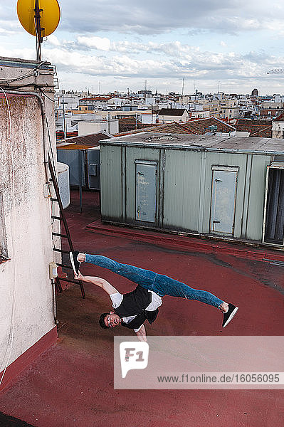 Young man breakdancing on building terrace in city