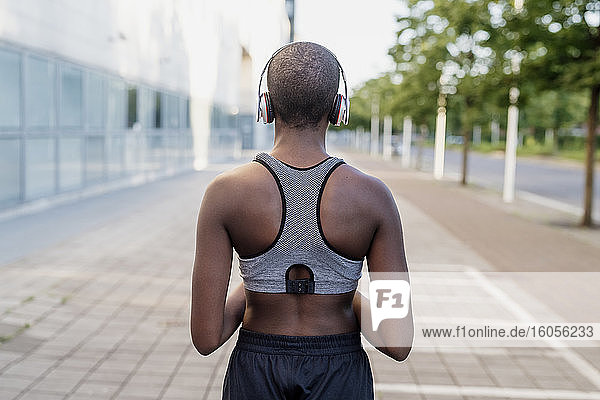 Young woman with shaved head listening music through headphones while standing on footpath