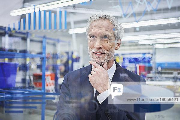 Selbstbewusster männlicher Manager mit Hand am Kinn  der auf Grafiken auf einem Glas in der Industrie schaut Selbstbewusster männlicher Manager mit Hand am Kinn, der auf Grafiken auf einem Glas in der Industrie schaut