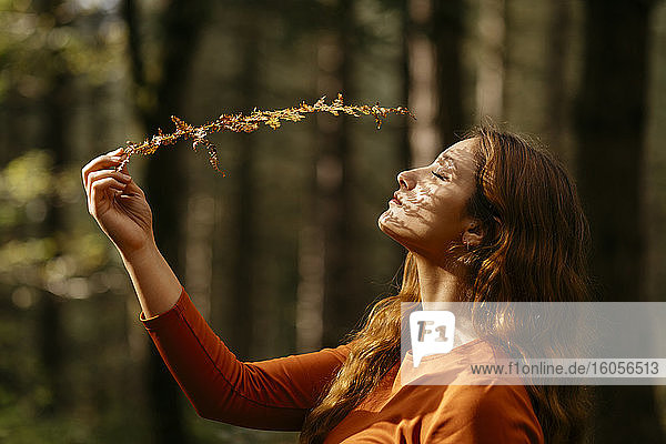 Nahaufnahme einer schönen Frau mit geschlossenen Augen  die eine Pflanze im Wald hält