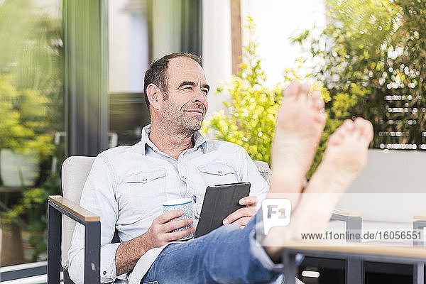 Relaxed mature man sitting with coffee cup and digital tablet while looking away in back yard