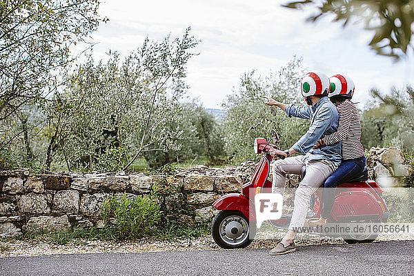 Junges Paar erkundet die Toskana auf einer Vespa  Italien Junges Paar erkundet die Toskana auf einer Vespa, Italien