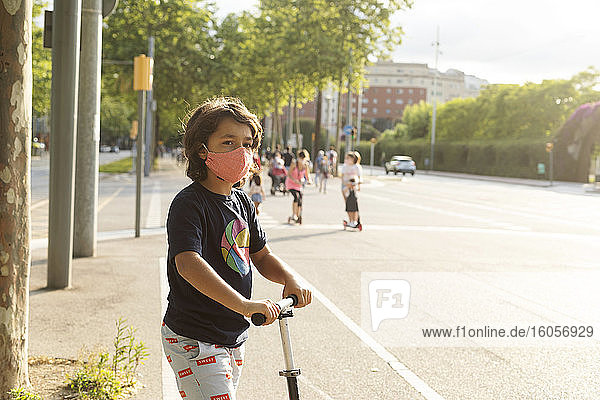 Portrait of boy wearing protective mask riding scooter in the city
