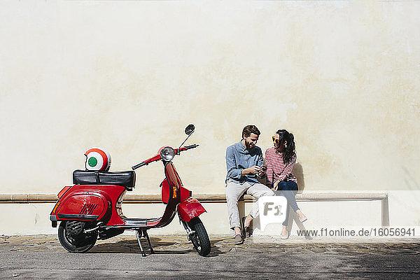 Mann benutzt sein Smartphone  während er mit seiner Freundin auf dem Sitz an der Wand sitzt Mann benutzt sein Smartphone, während er mit seiner Freundin auf dem Sitz an der Wand sitzt