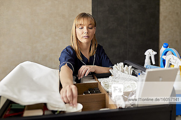 Zimmermädchen ordnet Reinigungsmittel auf einem Rollwagen  während sie im Hotelkorridor steht Zimmermädchen ordnet Reinigungsmittel auf einem Rollwagen, während sie im Hotelkorridor steht