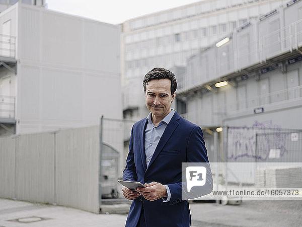 Porträt eines selbstbewussten reifen Geschäftsmannes mit Tablet auf einer Baustelle