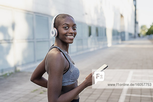 Smiling young woman wearing headphones using smart phone while standing in city