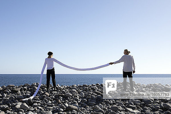 Woman with long artificial arms holding man's hand at beach against clear sky