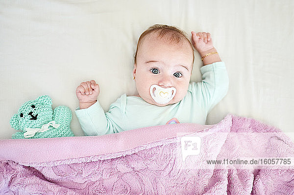 Porträt eines kleinen Mädchens mit Schnuller und Kuscheltier auf dem Bett liegend Porträt eines kleinen Mädchens mit Schnuller und Kuscheltier auf dem Bett liegend