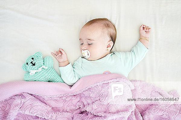Porträt eines schlafenden kleinen Mädchens mit Schnuller und Kuscheltier Porträt eines schlafenden kleinen Mädchens mit Schnuller und Kuscheltier