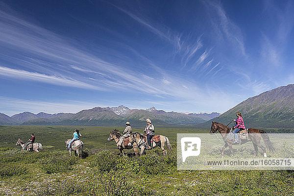 Besucher auf einem Ausritt aus der Rainy Pass Lodge vor dem Hintergrund der Alaska Range  Süd-Zentral-Alaska  Sommer