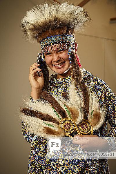 Halbjupik-Eskimo 12-jähriges Mädchen in traditionellem Kopfschmuck und Kuspuk mit Pelz und Grastanz Fans sprechen per Handy im Kulturzentrum  Bethel  Alaska