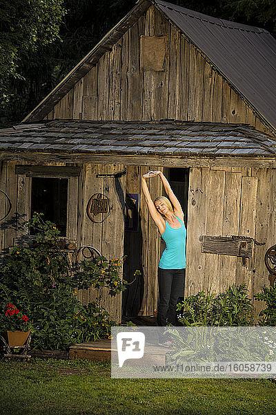 Frau streckt sich vor einer rustikalen Hütte in Girdwood  Süd-Zentral-Alaska  Sommer