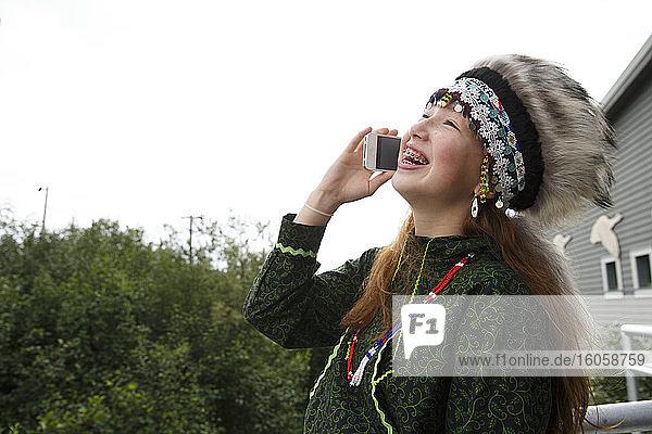 Halbjupik-Eskimo 14-jähriges Mädchen in traditioneller Kopfbedeckung und Kuspuk mit Smartphone / Handy vor dem Kulturzentrum  Bethel  Alaska