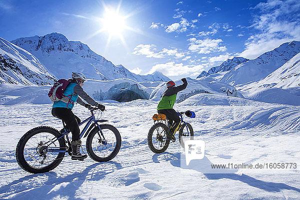 Zwei fette Radfahrerinnen vor dem Skookum-Gletscher  Chugach National Forest  Alaska an einem sonnigen Wintertag  die beim Vorbeifahren mit der Faust pumpen  Süd-Zentral-Alaska; Alaska  Vereinigte Staaten von Amerika