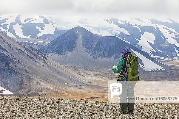 Frau mit Rucksack und Karte mit dem Berg Katmai im Hintergrund  Valley of Ten Thousand Smokes  Katmai National Park and Preserve  Südwest-Alaska; Alaska  Vereinigte Staaten von Amerika