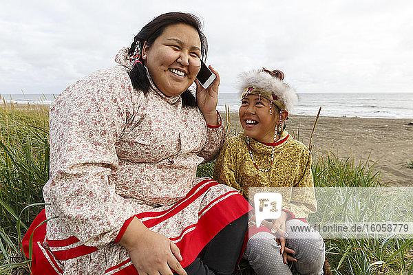 Yupik-Eskimo-Mädchen  in traditioneller Kleidung  Gespräch über Smartphone / Handy im Gras entlang der Bering-See-Küste  Nome  Alaska  Sommer