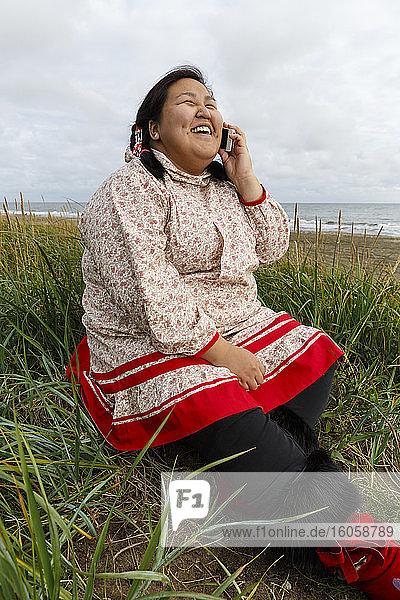 Yupik Eskimo-Mädchen  in traditioneller Kleidung  Gespräche über Smartphone / Handy im Gras entlang der Bering-See-Küste  Nome  Alaska  Sommer