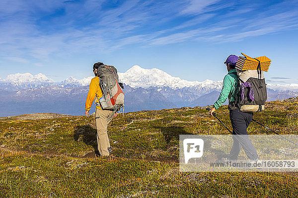 Frau und Mann mit Rucksack auf der Tundra in Richtung Denali und Alaska Range  entlang des Kesugi Ridge Trail  Denali State Park  an einem sonnigen Herbsttag  Süd-Zentral-Alaska; Alaska  Vereinigte Staaten von Amerika