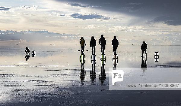 Touristen posieren in der Reflexion während der Regenzeit (Dezember-Februar) im Salar de Uyuni  der größten Salzfläche der Welt; Abteilung Potosi  Bolivien