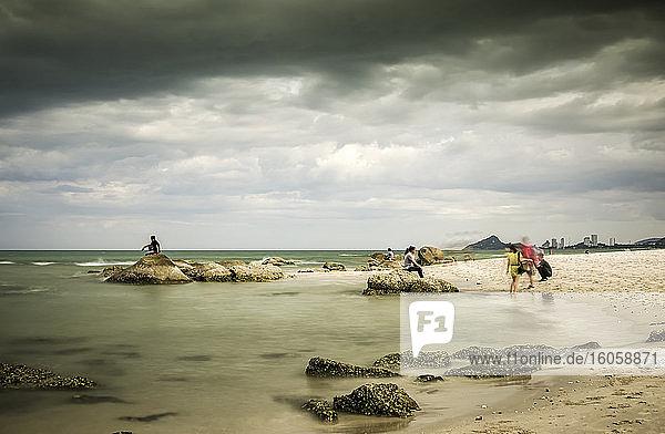 Küstenurlaubsgebiet in Thailand mit Touristen am Wasser auf weißem Sand und Felsen; Hua Hin  Prachuap Khiri Khan  Thailand